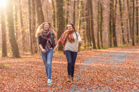 camaraderie: Two joyful women running hand in hand through a wooded autumn park with colorful leaves lying on the ground in a healthy lifestyle concept