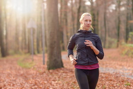cardiovascular workout: Pretty fit young woman jogging through autumn or fall woodland approaching the camera, close up upper body portrait in a healthy lifestyle concept