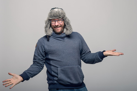 exultant: Happy man wearing glasses and a winter hat cheering and celebrating  with an exultant expression, over grey with copy space