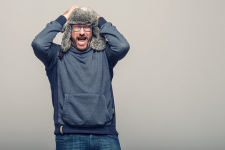 glasses eye: Middle-aged reacting in shock and horror with her mouth agape and hands raised to her cheeks as she looks sideways to the left of the frame, over grey Stock Photo
