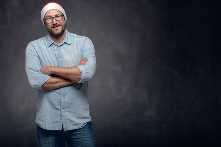 santa clause hat: Three Quarter Shot of a Middle Aged Man, Wearing Santa Clause Hat, Smiling at the Camera, with Arms Crossing Over his Chest, Against Grey Gradient Background. Stock Photo