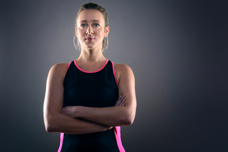 woman posing: Head and Shoulders Portrait of Confident Athletic Blond Woman Wearing Pink and Black Tank Top and Standing with Hands on Hips in Studio with Grey Background