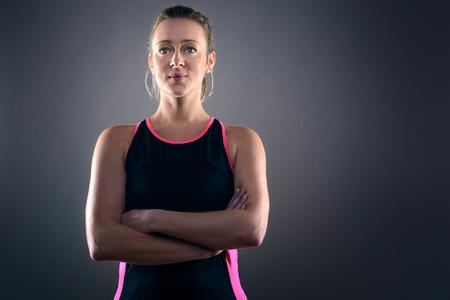 Kop en schouders portret van Zekere atletische blonde vrouw die roze en zwarte tank top en zich met handen op Heupen in Studio met Grijze Achtergrond
