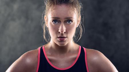 Hoofd en schouders portret van een zwetende atletische blonde vrouw die roze en zwarte tank top en staan met de handen op de heupen in Studio met Grijze Achtergrond Stockfoto