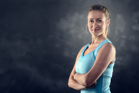 tourquoise: Head and Shoulders Portrait of an Athletic Blond Woman Wearing tourquoise Tank Top and Standing with crossed arms in Studio with Grey Background Stock Photo