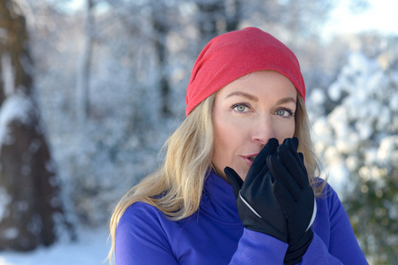 gloved: Pretty young blond woman blowing on her gloved hands to keep them warm in a cold snow winter park in morning sunshine