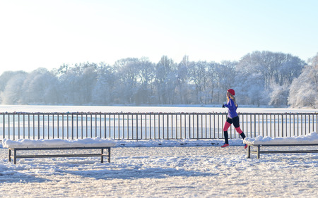 promenade: Young woman running in winter snow along a promenade overlooking the ocean as she enjoys the invigorating cold weather in a healthy active lifestyle concept, panoramic view