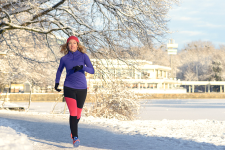 jogging: Full Body Shot of a Pretty Athletic Woman Jogging in winter with earphones and winter attire, Smiling at the Camera, with copy space Stock Photo