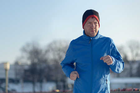men running: Man out in winter weather for his daily run jogging alongside a railing in a snowy landscape in a fitness and healthy lifestyle concept, close up upper body
