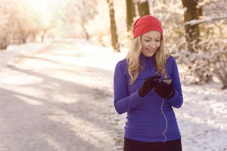 pone: Woman checking her mobile pone for text messages with a happy smile as she enjoys a healthy winter walk through a snowy park in early morning sunshine