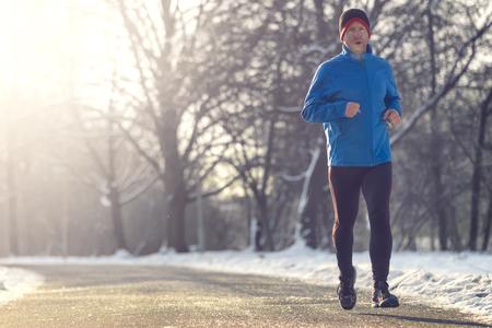 El hombre a cabo en tiempo de invierno por su carrera diaria corre por la carretera pavimentada en un paisaje nevado en un gimnasio y el concepto de estilo de vida saludable, de cerca de cuerpo completo