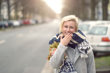 upper body: Smiling attractive young blond woman in a woolly scarf standing at the side of an urban street looking at the camera, upper body view