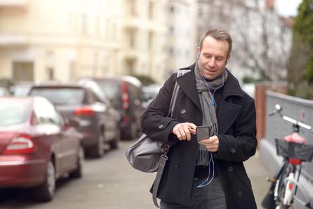 Aantrekkelijke man in de winter mode status controleren van zijn mobiele telefoon voor berichten of het maken van een oproep in een stedelijke straat, close-up bovenlichaam view