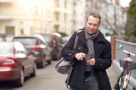 winter fashion: Attractive man in winter fashion standing checking his mobile phone for messages or making a call in an urban street, close up upper body view Stock Photo