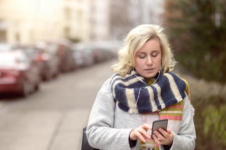 Attractive femme à la mode d'hiver debout vérifier son téléphone portable pour les messages ou faire un appel dans une rue urbaine, vue rapprochée du haut du corps