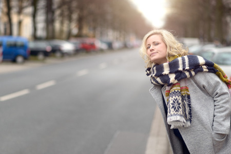 peering: Attractive blond woman in warm stylish winter fashion waiting for a cab or a lift peering anxiously down an urban street with an impatient expression