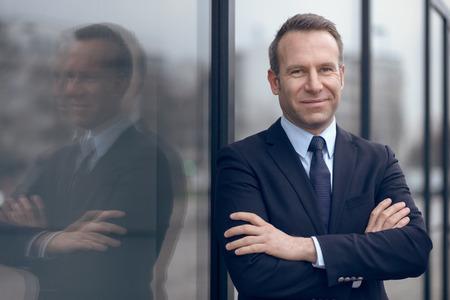 traje formal: Individual masculino empresario seguro y guapo en traje azul y corbata con mueca apoyado en la ventana al aire libre