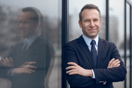 modern business: Single confident and handsome male businessman in blue suit and necktie with grin leaning on window outdoors