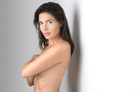 naked women: Single middle aged grinning woman in brown hair covering her chest with arms while leaning against white wall