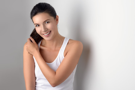 ponytails: Single cute woman in sleeveless blouse holding ponytails in her hands while standing near gray wall Stock Photo