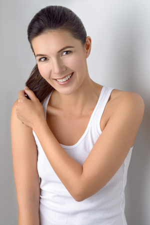 sleeveless: Single cute woman in sleeveless blouse holding ponytails in her hands while standing near gray wall Stock Photo