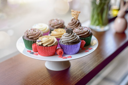 garnishments: Eight deliciously sweet cupcakes covered with creamed chocolate, vanilla and various other garnishments alongside little pink heart candies Stock Photo