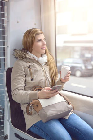 women jeans: Beautiful young blond woman in coat and long blond hair sitting on commuter train seat Stock Photo
