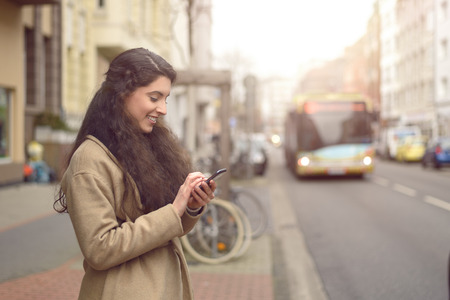 mobile business: Texting brunette woman reads a message on her mobile phone and smiles while being unaware of approaching bus
