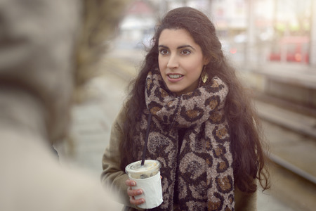 pretty brunette woman: Pretty young woman with long brunette hair wearing a soft winter scarf holding a takeaway beverage and staring to the side of the camera Stock Photo