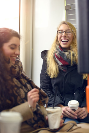 seated: Two seated blond and brunette female friends wearing coats and holding coffee share a humorous moment