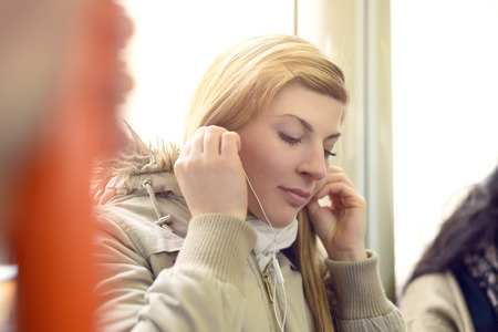 buss: Single beautiful young woman in coat and scarf using earphones while sitting on buss or train