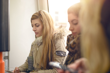 crowded space: Single blond woman in gray winter coat sitting inside crowded commuter train or bus in front of window Stock Photo