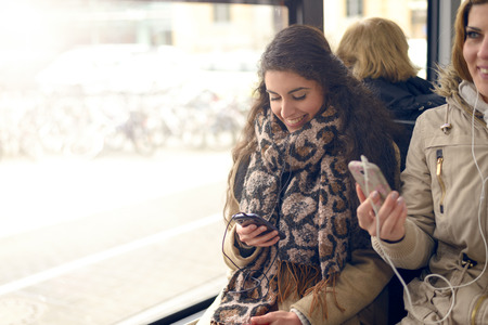public transport: Happy brunette woman reading a message on her mobile phone while sitting in a bus, public transport and technology concept
