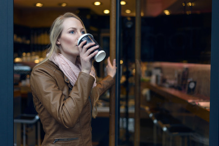 sipping: Young blond woman in brown leather jacket and scarf sipping coffee from cup near door of bistro