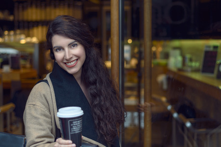 woollen: Young brunette woman in brown woollen jacket and scarf sipping coffee from cup near door of bistro