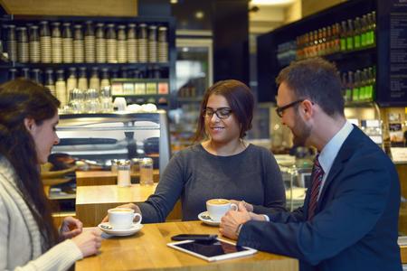mujeres sentadas: La sonrisa del caf� que sirve camarera de dos mujeres j�venes sentados en una mesa en un restaurante o restaurante