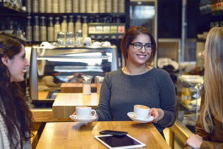mujeres sentadas: La sonrisa del café que sirve camarera de dos mujeres jóvenes sentados en una mesa en un restaurante o restaurante