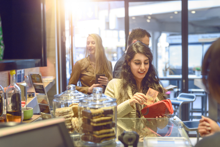 to till: View over the shoulder of the cashier of an attractive young blond woman making payment at a till looking in her purse Stock Photo