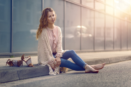 kerb: Serious pretty trendy young woman sitting relaxing on a sidewalk on an urban street in her high heels and fashionable outfit