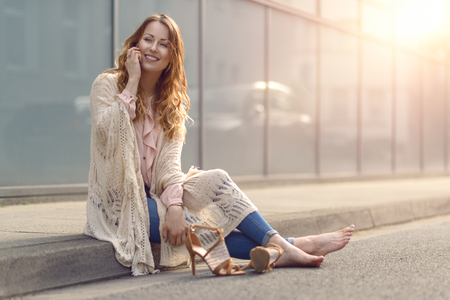 Trendy young woman sitting on the side of a street with her high heeled shoes off relaxing and smiling while chatting on her mobile phone Stock Photo