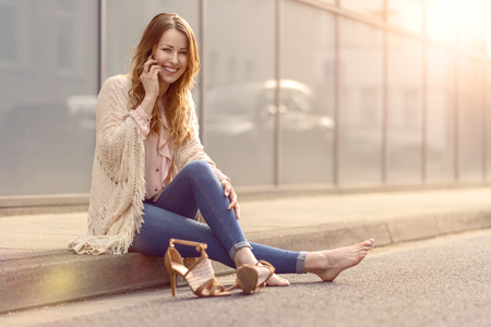 high heeled shoes: Trendy young woman sitting on the side of a street with her high heeled shoes off relaxing and smiling while chatting on her mobile phone Stock Photo