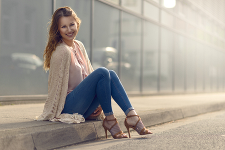 kerb: Smiling pretty trendy young woman sitting relaxing on a sidewalk on an urban street in her high heels and fashionable outfit smiling at the camera