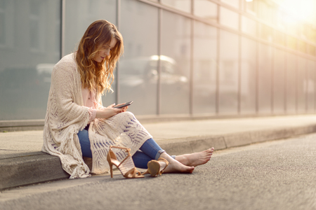 kerb: Attractive trendy woman sitting on the kerb of an urban street with her high heeled shoes lying on the ground alongside her as she reads an sms on her mobile phone, with copy space