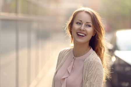 Bonne jeune femme en riant vers la caméra en plein matin lumière du soleil en plein air avec copie espace la gauche