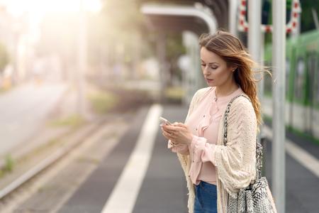 Aantrekkelijke modieuze jonge vrouw te wachten alleen op een platform op een kleine stedelijke station controle van haar mobiele telefoon voor berichten