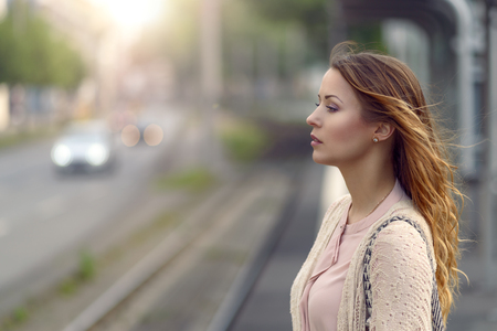 Young woman standing waiting at a railway station on a deserted open-air platform alongside a road with traffic, close up head and shoulders side view