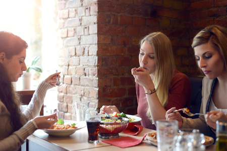 lunch table: Three attractive young women friends relaxing over lunch together in a restaurant sitting at a table chatting and enjoying their food Stock Photo