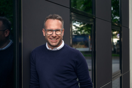 Handsome smiling middle aged man wearing eyeglasses and sweater leaning against building outside with trees reflecting in window