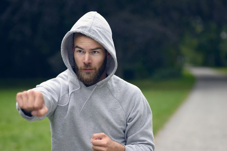 upper body: Young bearded man wearing a grey hoodie working out in a park punching air with his fist , close up upper body with copy space