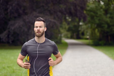 Fit bearded young man jogging through a park listening to music on his mobile phone, upper body approaching the camera with copy space 스톡 콘텐츠